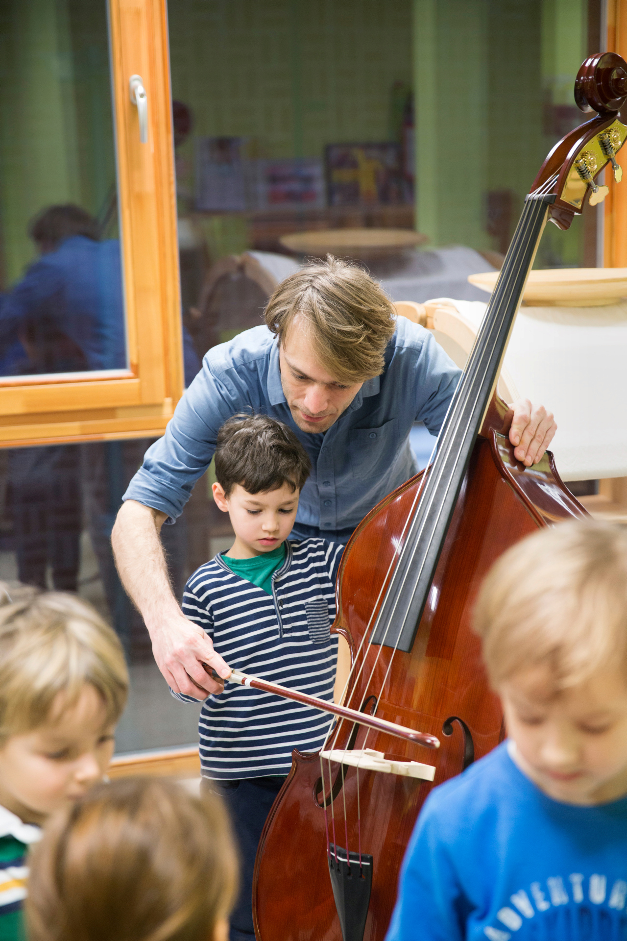 Jonas Danielowski helps a youngster play the double bass