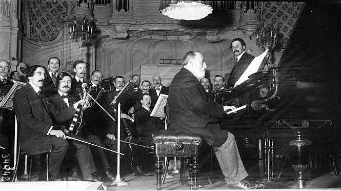 Camillle Saint-Saëns am Klavier in der Pariser Salle Gaveau, 1913, ringsum sitzt das Orchester.