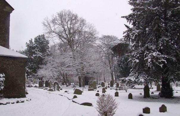 schneebedeckter alter Friedhof