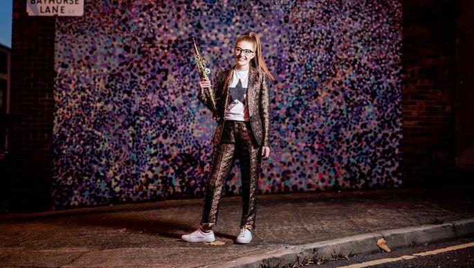 Jess Gillam, lachend, mit Saxofon.