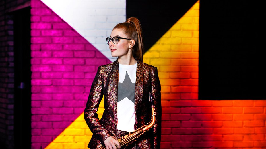 Jess Gillam mit ihrem Saxofon vor einer bunten Wand, zur Seite blickend.